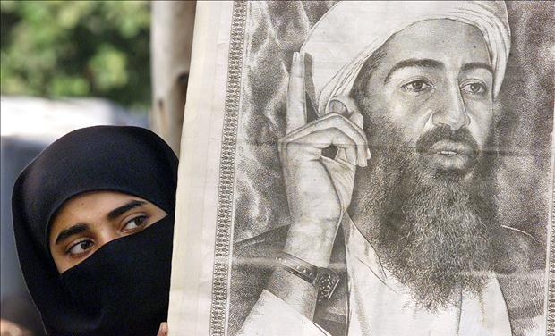 A PAKISTANI WOMAN PEERS AROUND A POSTER OF OSAMA BIN LADEN IN KARACHI.