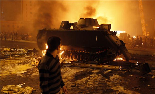 A protester looks at a burnt Egyptian Army armoured vehicle in downtown Cairo